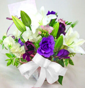 紫の花の春のアレンジメント(白リボン)